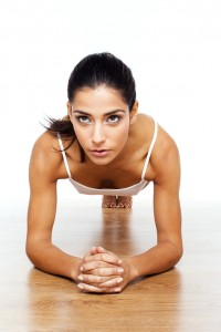 Athletic Girl Doing Stretching Exercises, facing camera outstretched on floor.