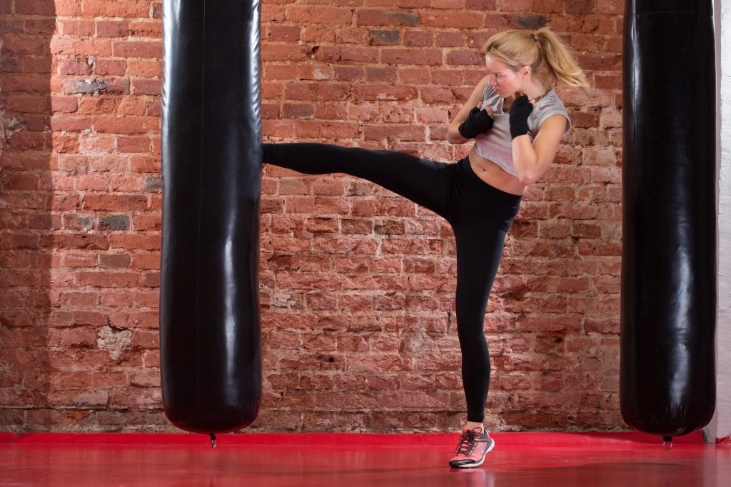 Girl Kicking At Punching Bag Iron Fit